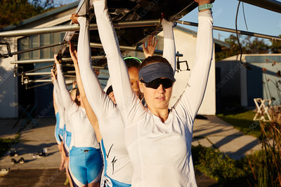 Confident rowing team lifting scull overhead