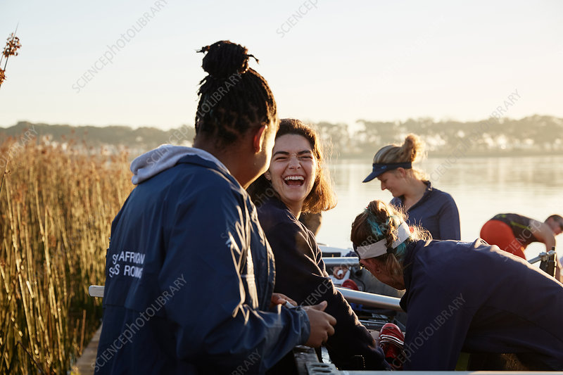 Female rowers laughing at lakeside