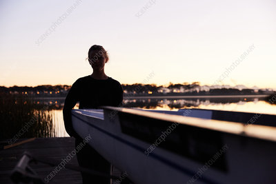 Silhouette of rower on sunrise lakeside dock