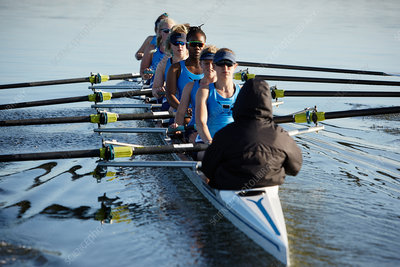 Female rowers rowing scull on lake