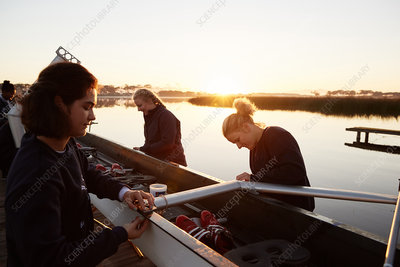 Female rowers preparing scull at sunrise lakeside