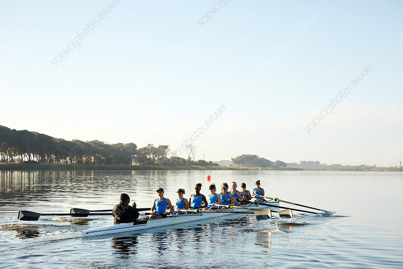 Female rowers rowing scull on lake below blue sky