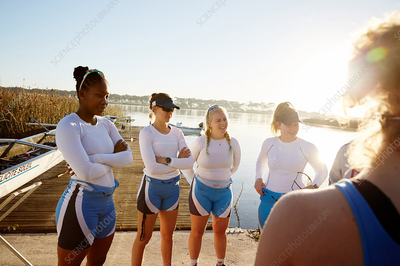 Female rowers meeting at sunny lakeside