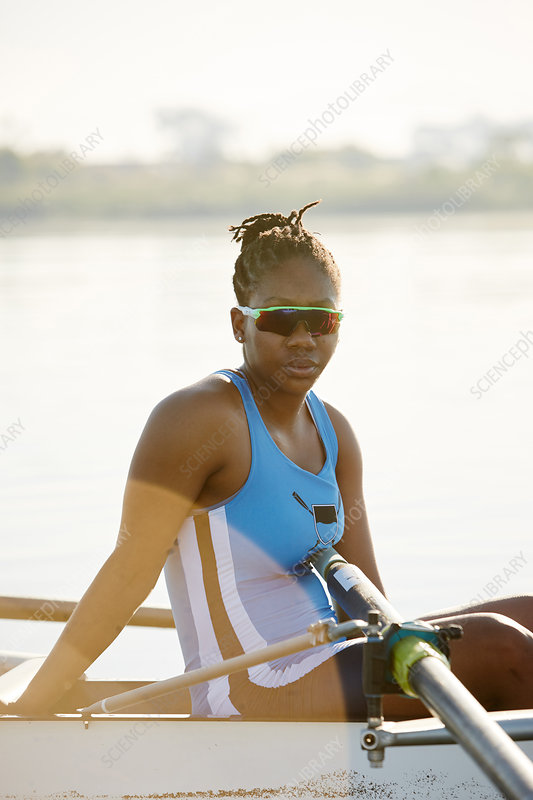 Portrait confident female rower in scull on lake