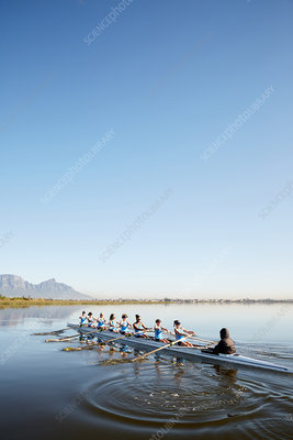 Female rowers rowing scull on tranquil lake
