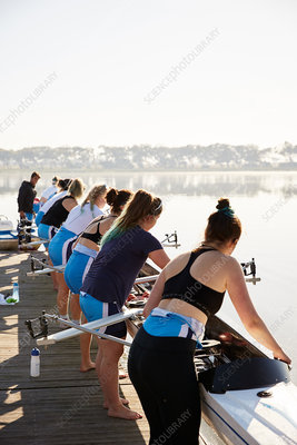 Female rowers lowering scull from lakeside dock