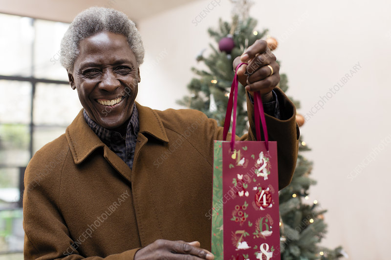 Portrait smiling senior man with Christmas gift
