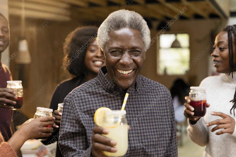 Portrait senior man drinking lemonade with family