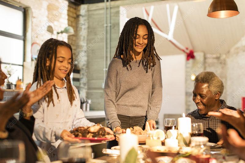 Multi-generation family serving Christmas dinner