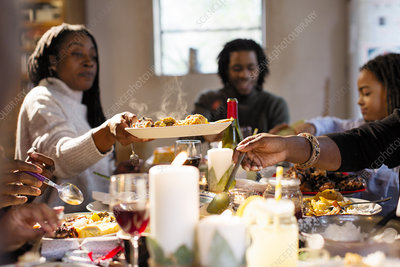 Woman passing food at Christmas dinner