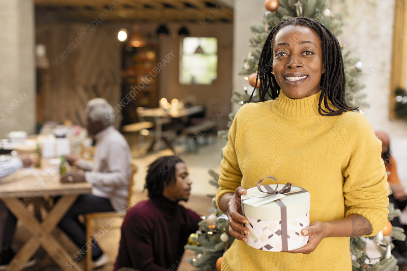 Portrait smiling woman holding Christmas gift