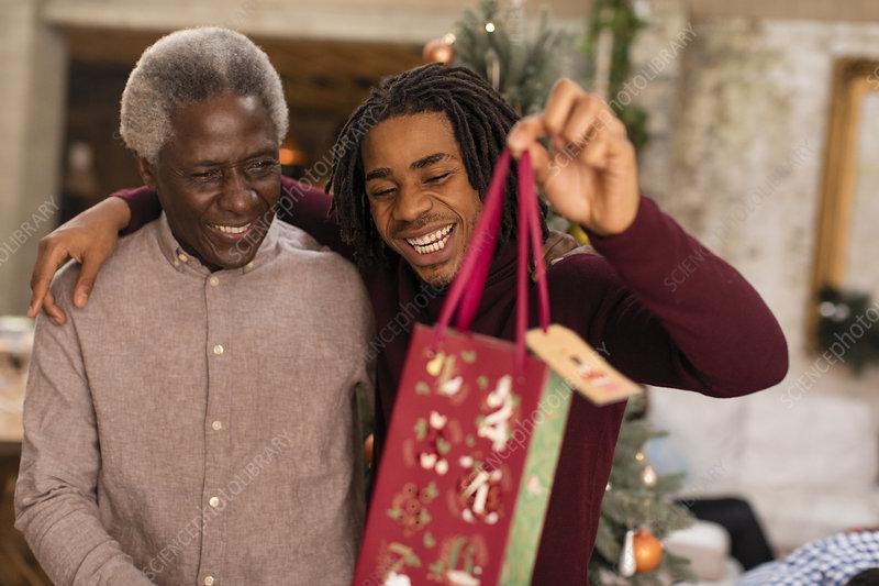 Grandson giving Christmas gift to grandfather