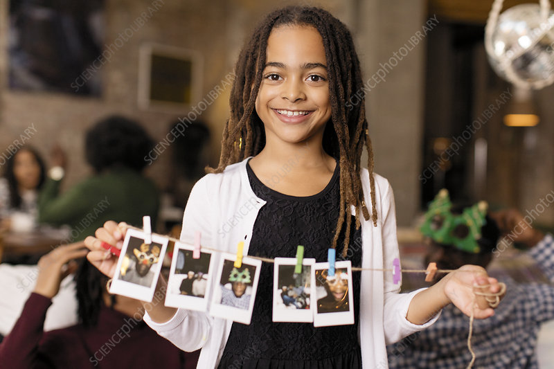 Portrait girl holding string of instant photos