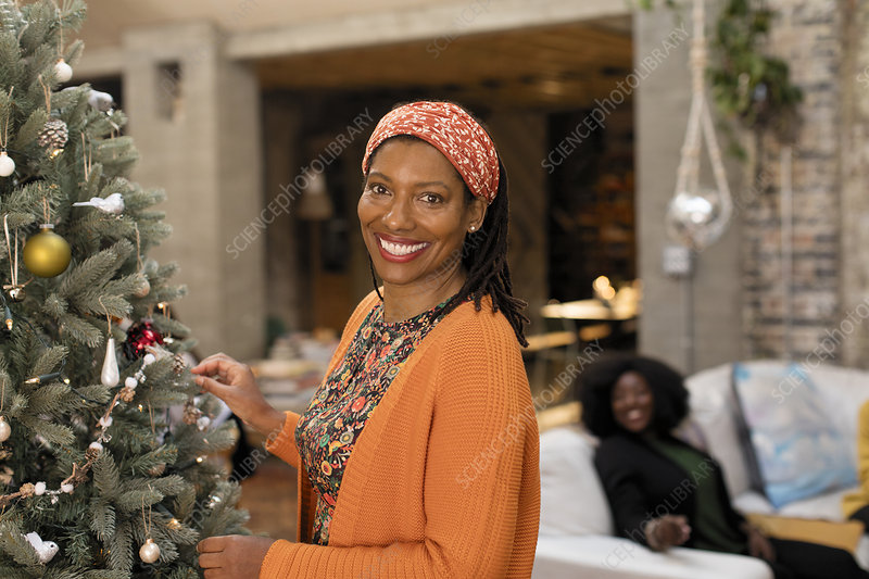 Portrait smiling woman decorating Christmas tree