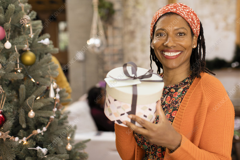 Portrait woman holding gift next to Christmas tree