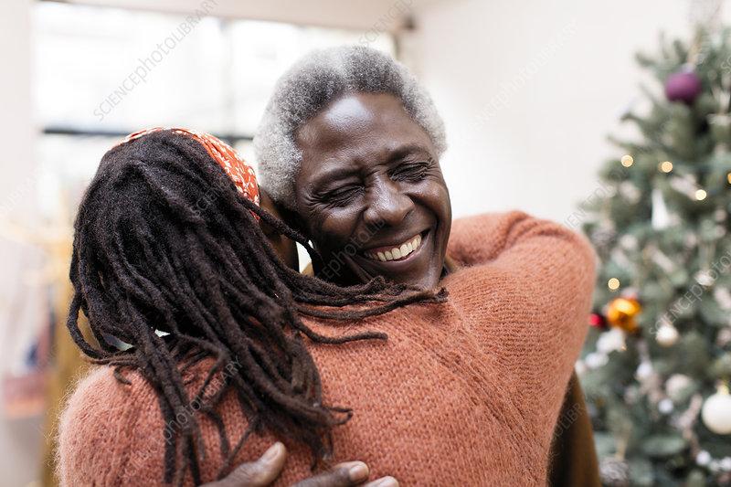 Happy senior couple hugging near Christmas tree