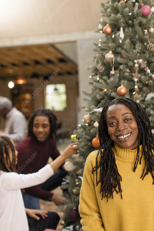 Mother decorating Christmas tree with children