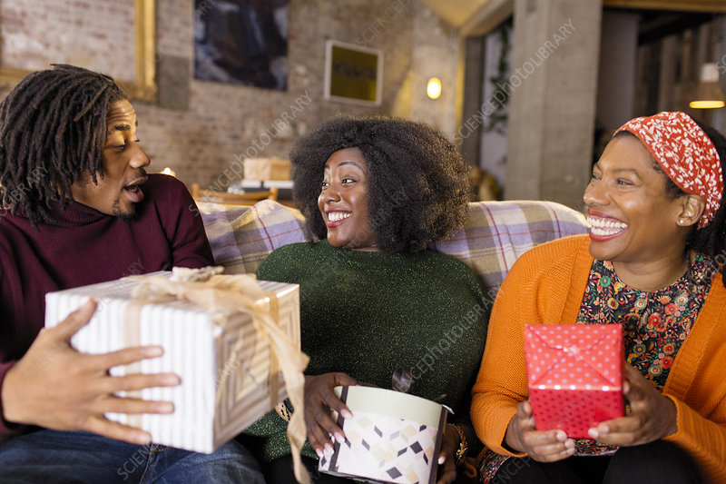 Enthusiastic family opening Christmas gifts