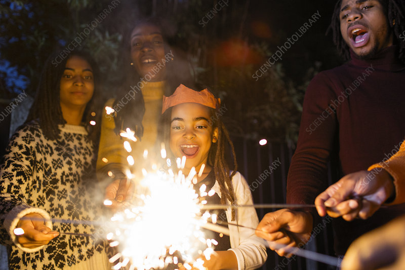Playful girl with sparkler celebrating with family