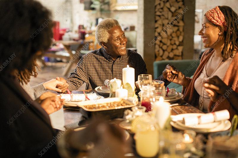 Family holding hands, praying at Christmas dinner