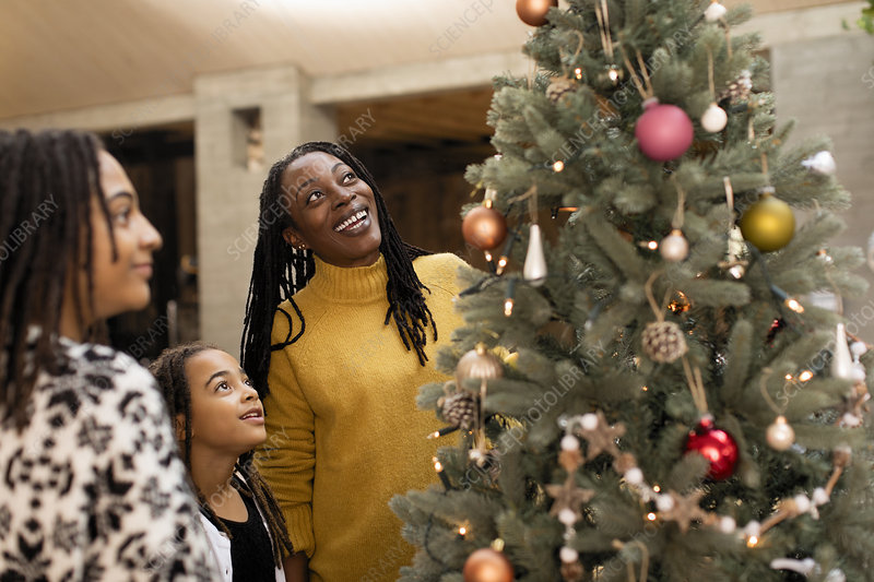 Mother and daughters looking up at Christmas tree