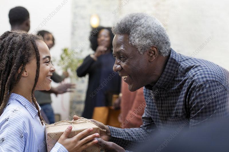 Grandfather giving Christmas gift to granddaughter