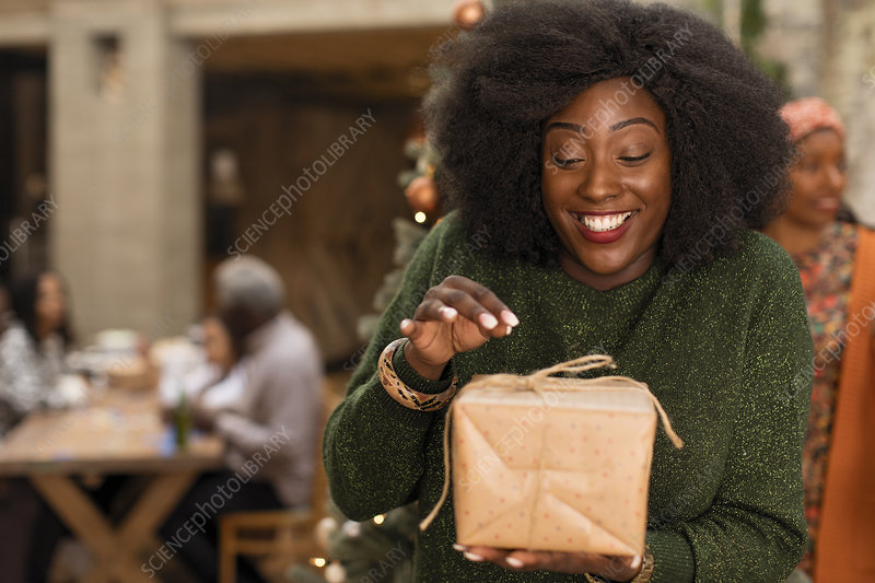 Curious young woman opening Christmas gift