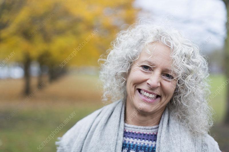 Portrait smiling senior woman in autumn park