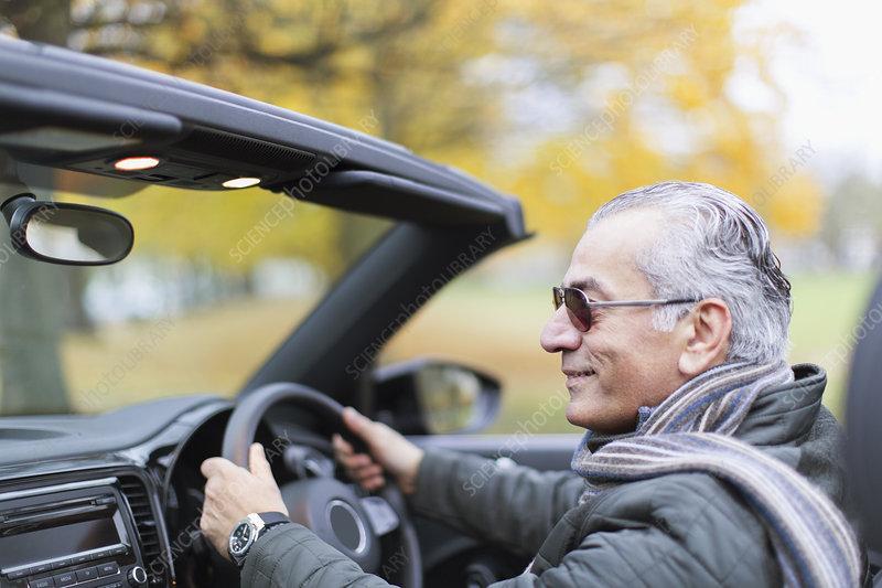 Senior man driving convertible