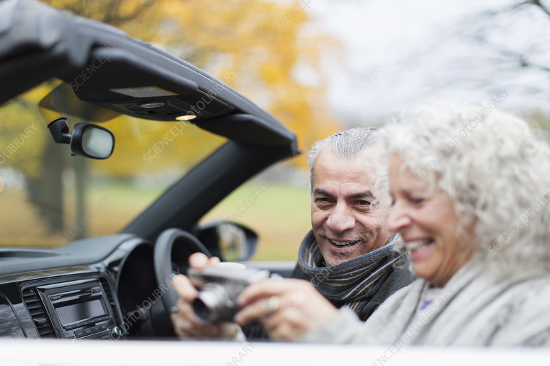 Senior couple using digital camera in convertible
