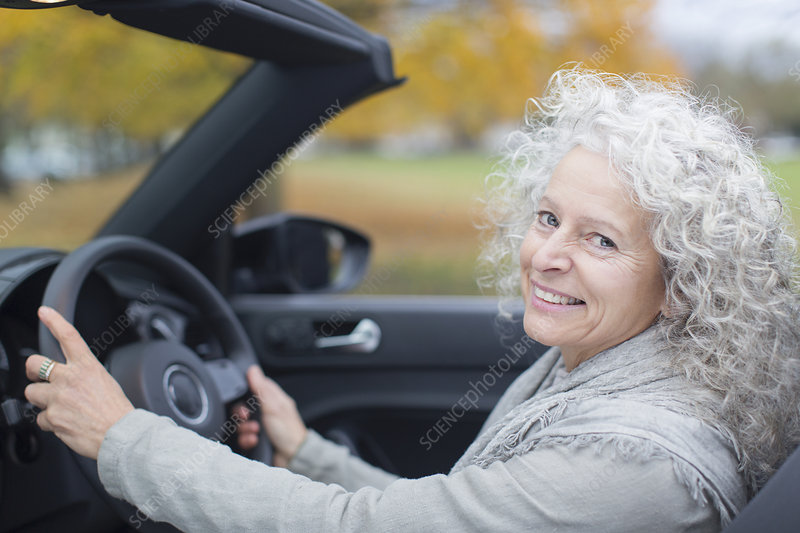 Portrait smiling senior woman driving convertible