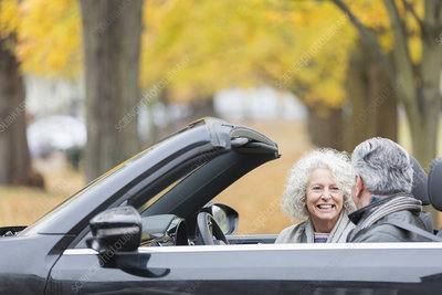 Smiling senior couple talking in convertible