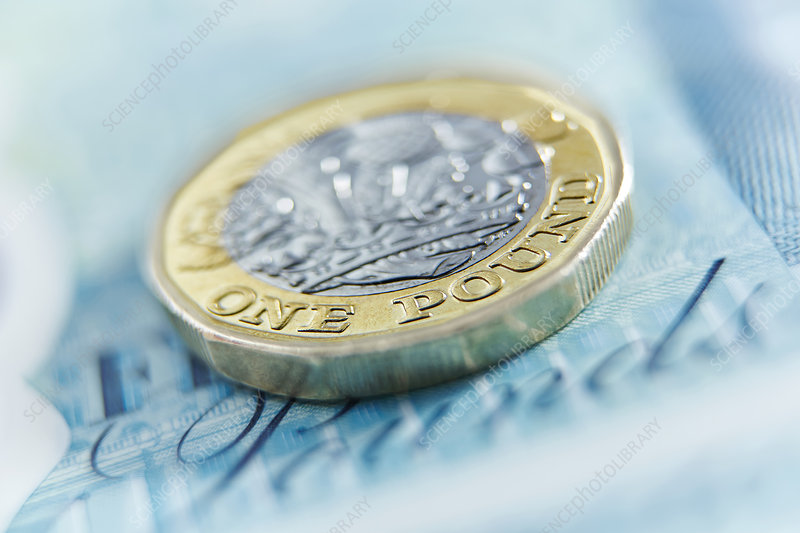 Close up one pound coin on five pound note