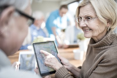 Seniors looking at photos on tablet