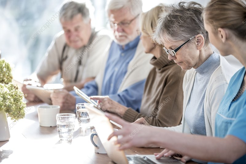 Seniors using tablets with carer