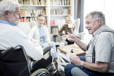 Senior man in wheelchair talking to friend