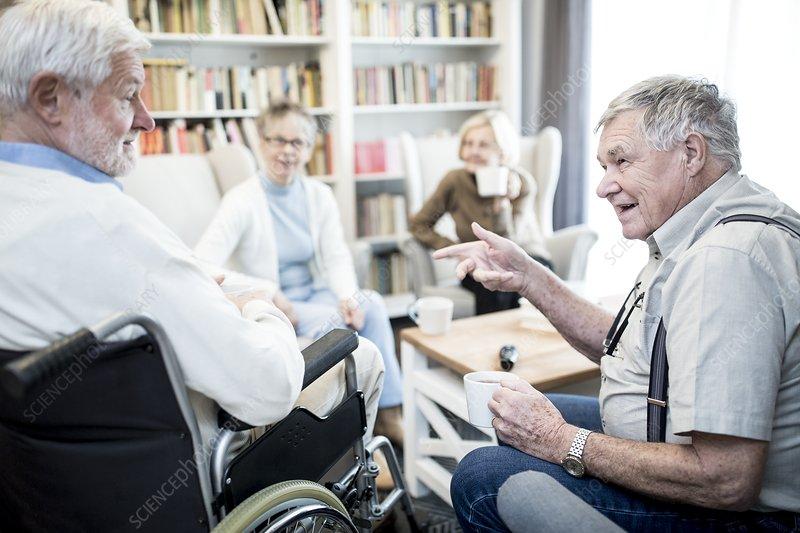 Senior man in wheelchair talking to friend