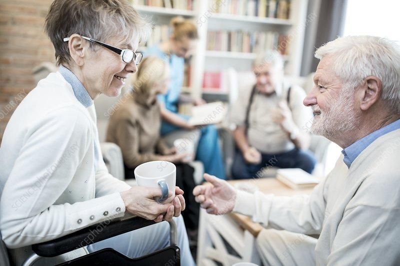 Woman in wheelchair talking to male friend