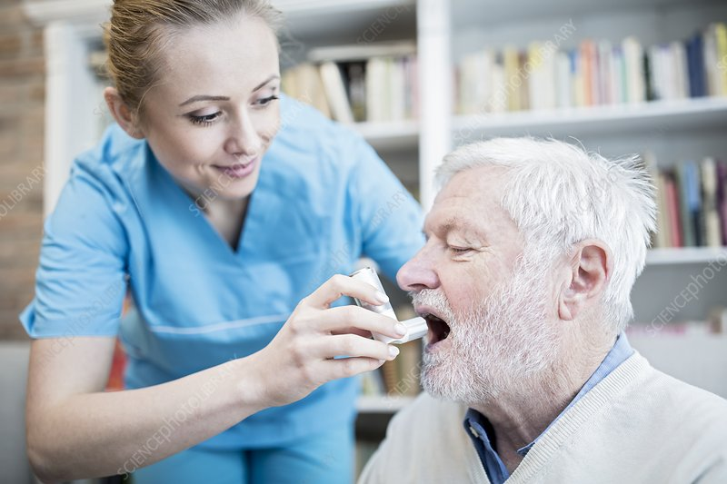 Carer helping senior man with inhaler