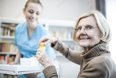 Woman opening medicine bottle and smiling