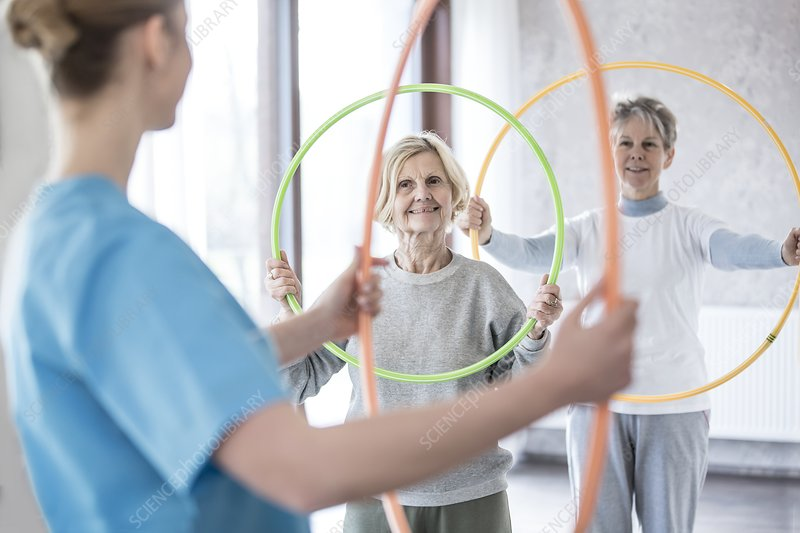Physiotherapist with women holding plastic hoops