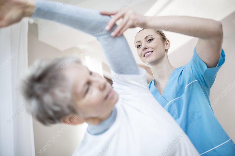 Woman stretching with physiotherapist
