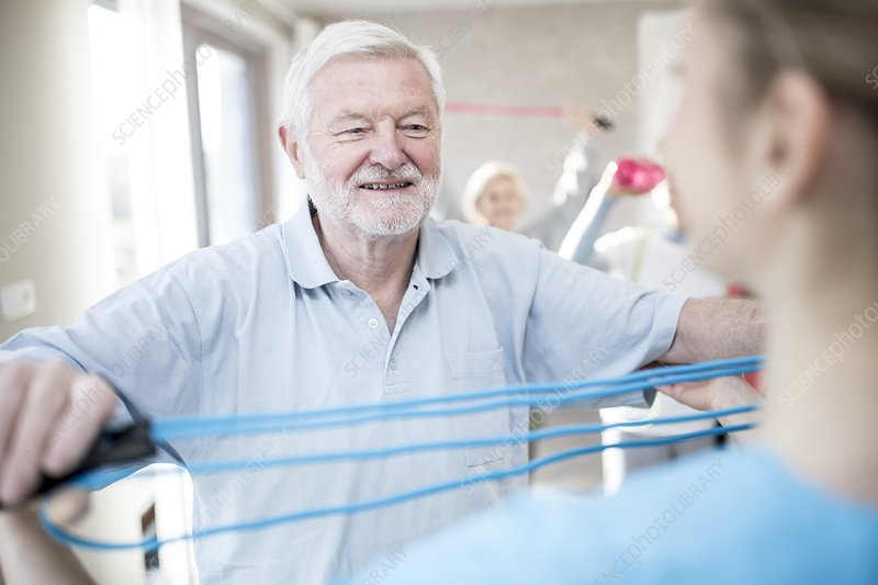 Senior man using resistance band in exercise class