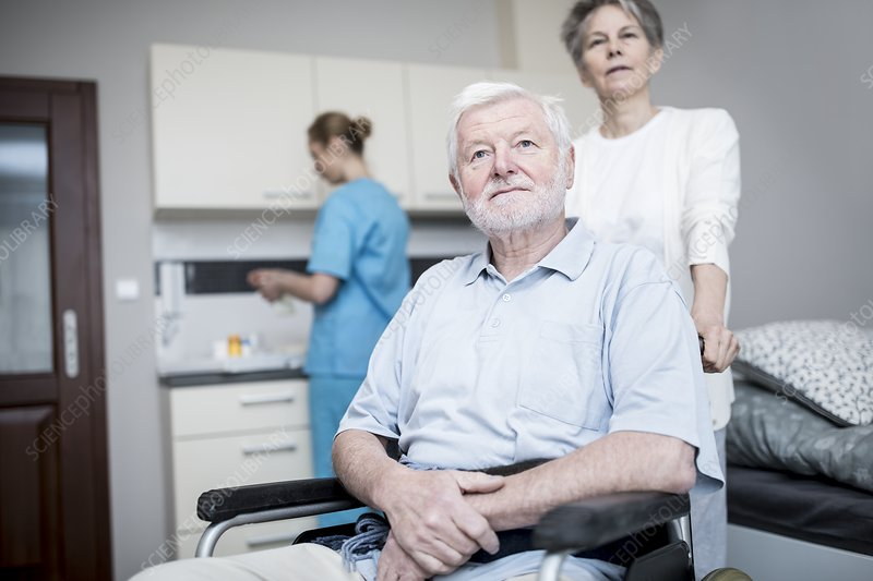 Senior man in wheelchair with woman