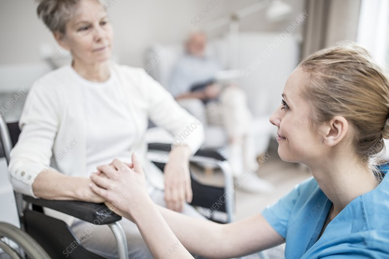 Carer reassuring senior woman in wheelchair