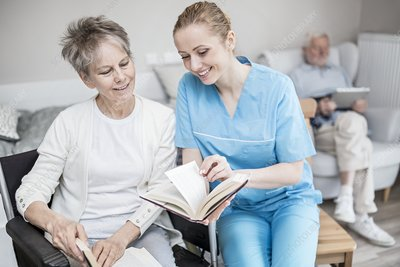 Carer reading book with woman