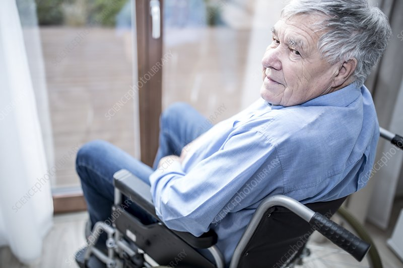 Senior man in wheelchair by window