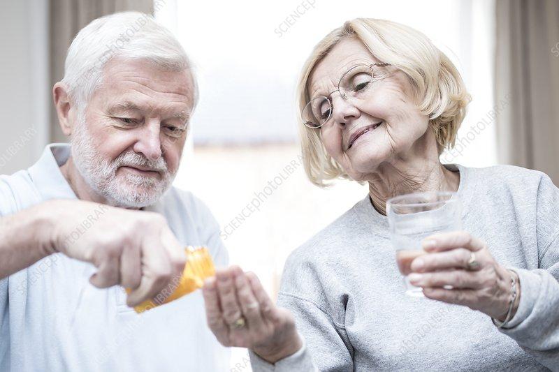 Senior man giving woman medication