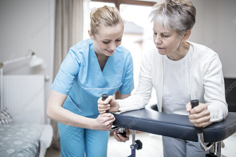 Woman using rollator with carer assisting