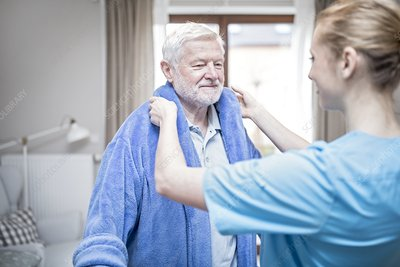 Carer helping man put on dressing gown